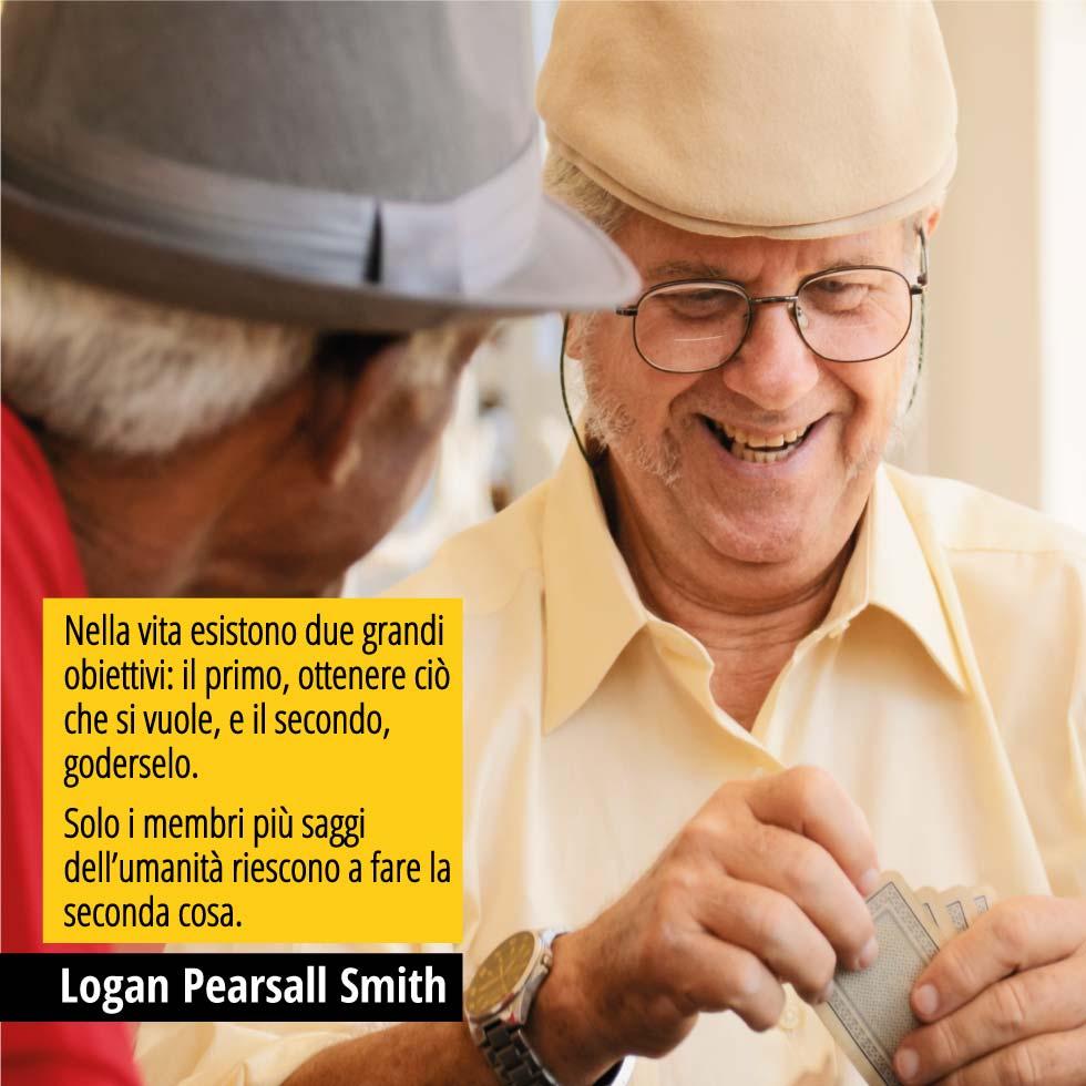 """In questa immagine due persone giocano a carte. Sono felici. In over una citazione di Logan Pearsall Smith. """"Nella vita esistono due grandi obiettivi: il primo, ottenere ciò che si vuole, e il secondo, goderselo. Solo i membri più saggi dell'umanità riescono a fare la seconda cosa."""""""